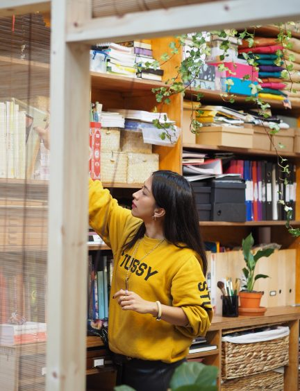 Woman reaching up to get something from a shelf